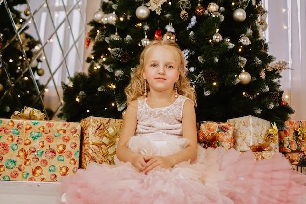 Fille dans une robe rose près de l'arbre de noël et des boîtes avec des cadeaux