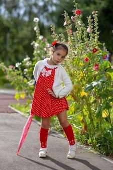 Fille dans une robe rouge et un chemisier blanc avec un parapluie de canne rose