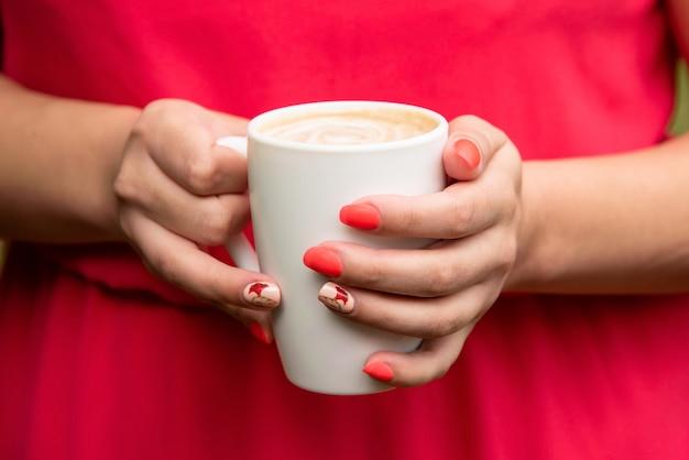 Fille dans une robe rouge tenant une tasse de café