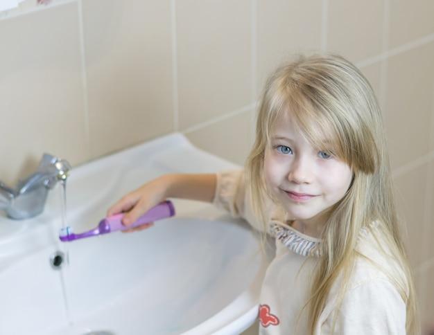 Fille dans une salle de bain lave une brosse à dents électrique.