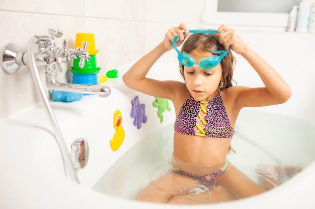 Une fille dans la salle de bain porte des lunettes de natation