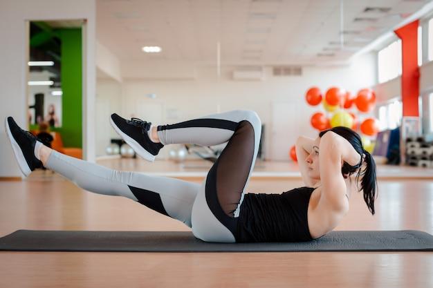 Fille dans la salle de gym faire des exercices de fitness.