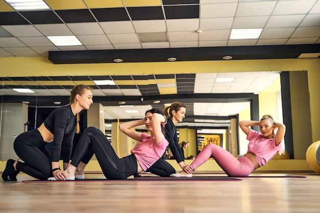 Fille dans la salle de gym faire des exercices pour le travail d'équipe de presse