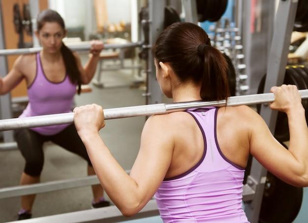 Fille dans la salle de gym lève la barre devant le miroir