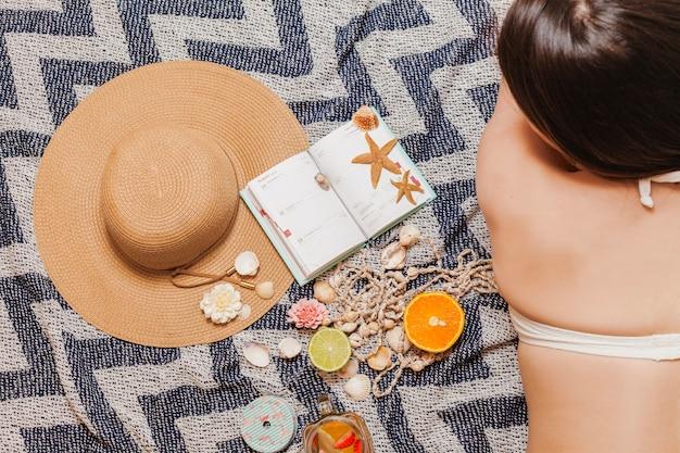 Fille dans une serviette de plage avec agenda et chapeau