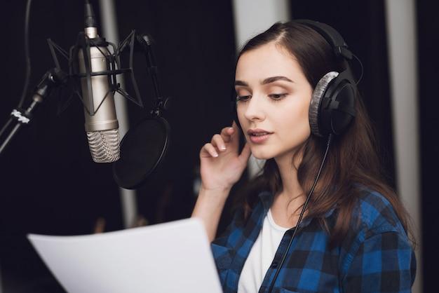 Fille dans le studio d'enregistrement chante une chanson.