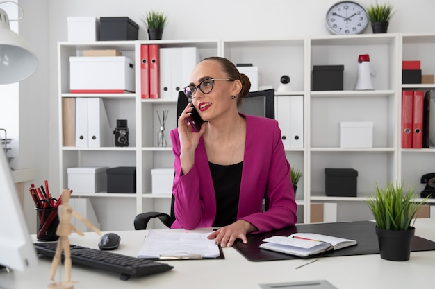 Fille dans le style des affaires, parler au téléphone au bureau