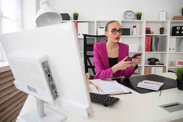 Une fille dans un style professionnel envoie des sms au téléphone au bureau