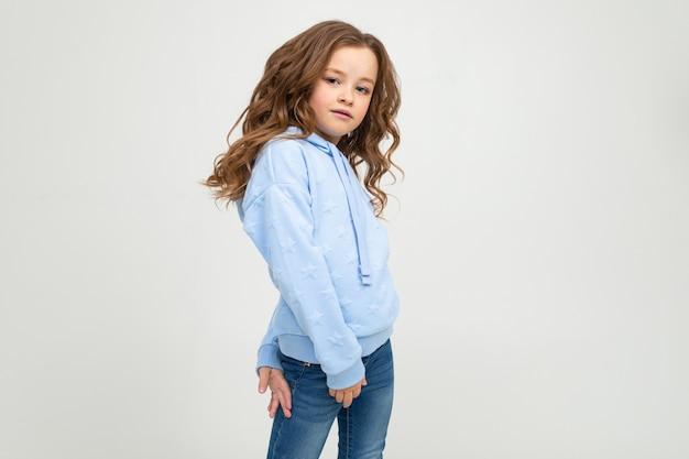 Fille dans un sweat à capuche bleu posant sur un mur clair avec un espace vide