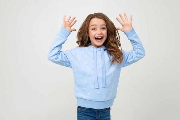 Fille dans un sweat à capuche bleu sourit joyeusement tout en tenant ses paumes devant elle sur un mur gris clair