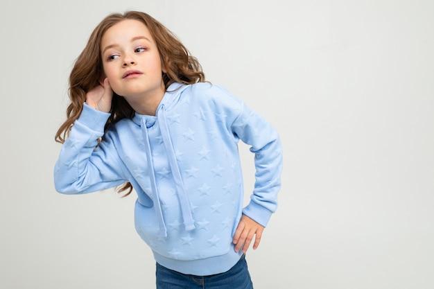 Une fille dans un sweat à capuche bleu tous les jours pressé écoute les sons tout en tenant ses mains par l'oreille sur un mur de studio lumineux