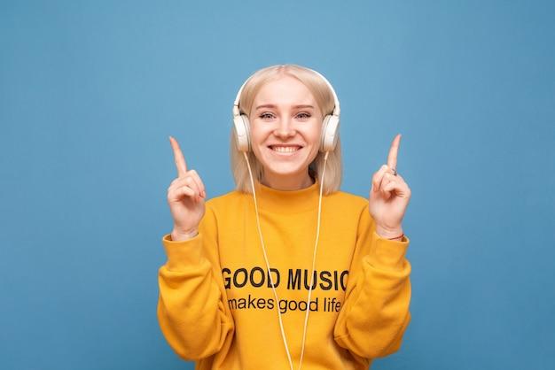 Fille dans un sweat-shirt orange écoute de la musique dans les écouteurs et montre les doigts