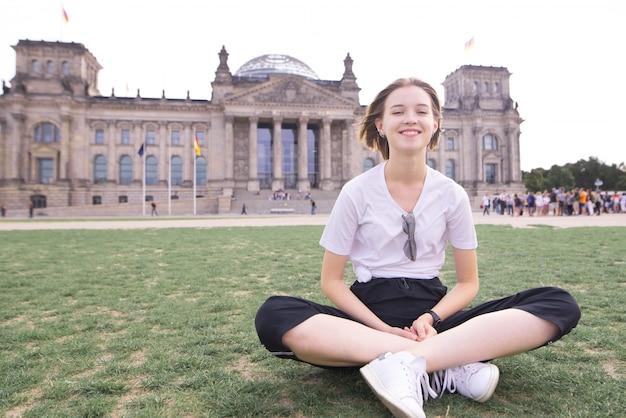 Fille dans un t-shirt blanc est assis sur la pelouse sur le fond du reichstag