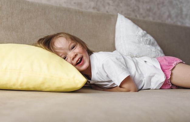 Une fille dans un t-shirt blanc se trouve à la maison sur le canapé et rit, posant sa tête sur un oreiller jaune