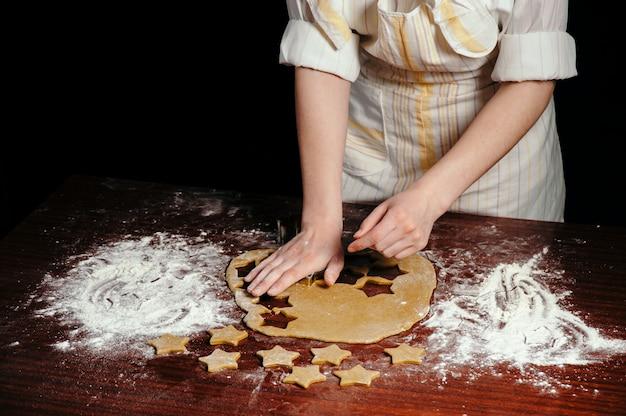 La fille dans un tablier coupe des biscuits en forme de pâte en forme d'étoiles sur une table en bois.