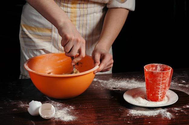 Une fille dans un tablier dans une cuisine sombre pétrit la pâte dans une tasse orange.