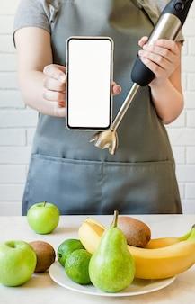 Fille dans un tablier tient une table de mixage et un smartphone. faire des smoothies aux fruits.