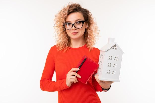 Fille dans des verres avec un ordinateur portable et une maquette d'une maison sur blanc