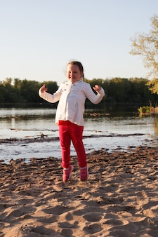 Une fille dans une veste blanche et un pantalon rose saute sur le sable sur la plage au bord du fleuve pendant le coucher du soleil.