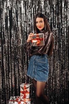 Une fille dans une veste brillante et une jupe avec des cadeaux sur un fond argenté sous forme de pluie.