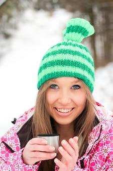Fille dans une veste cramoisie et un chapeau vert buvant du thé chaud à partir d'un thermos dans des montagnes enneigées