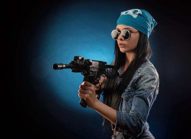 La fille dans une veste en denim avec un fusil automatique