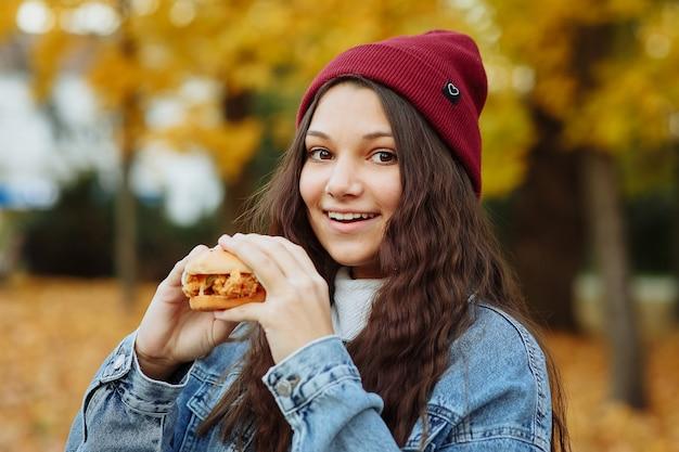 Une fille dans une veste en jean et un chapeau rouge avec un hamburger dans ses mains regarde la caméra et sourit