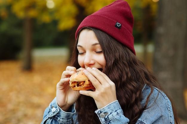 Une fille dans une veste en jean et un chapeau rouge mange un hamburger dans le parc en automne
