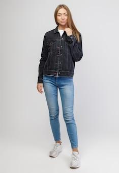 Fille dans une veste en jean noir et un pantalon en denim bleu sur fond blanc