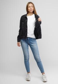Fille dans une veste en jean noir et un pantalon en jean bleu sur fond blanc.