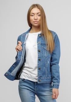 Fille dans une veste en jean et un pantalon en jean bleu sur fond blanc.