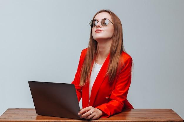Fille dans une veste rouge et des lunettes avec un ordinateur portable