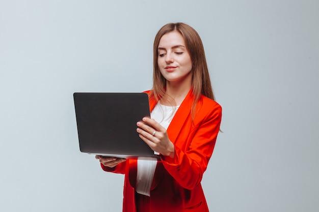 La fille dans une veste rouge tient un ordinateur portable sur un fond clair