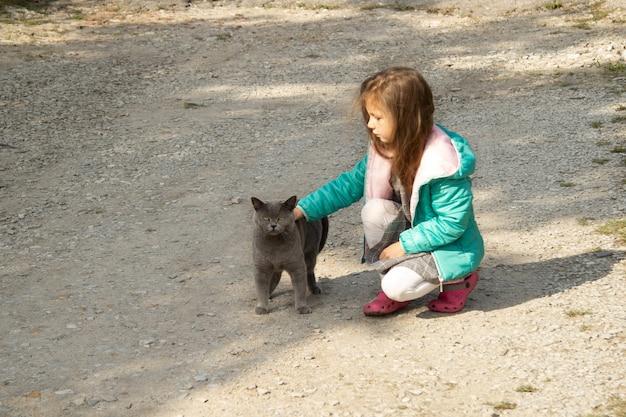 Une fille dans une veste verte assise avec son dos caresse un gros chat gris foncé dans la rue