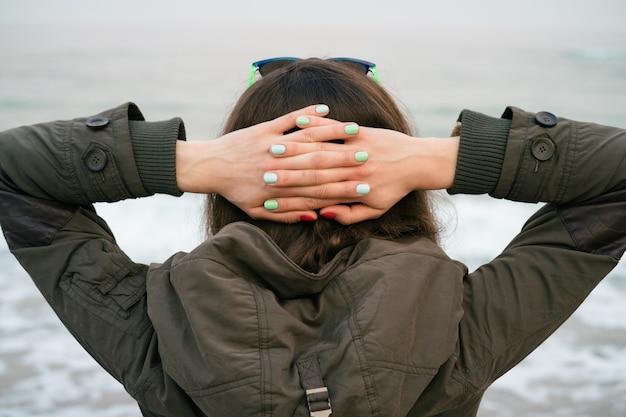 Fille dans la veste verte avec une capuche regarde la mer pose ses mains à l'arrière de la tête