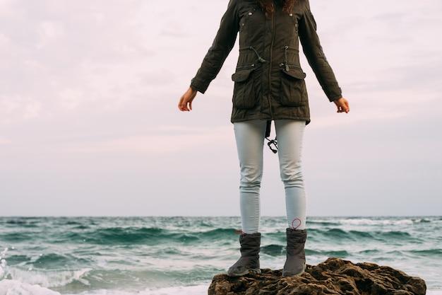 Fille dans la veste verte, jeans et bottes se dresse sur une pierre rocheuse sur la plage par temps nuageux