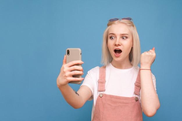 Fille dans un vêtement décontracté lumineux tient un smartphone dans ses mains, regarde l'écran du smartphone