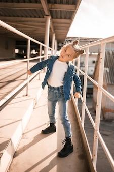 Fille dans des vêtements en jean dansant le hip-hop dans le parking