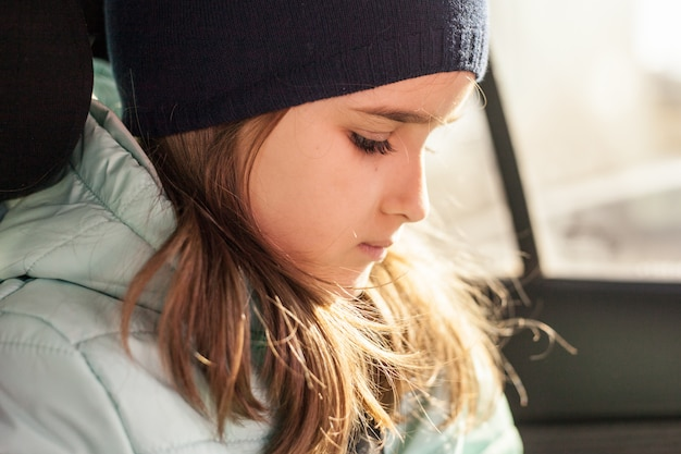 La fille dans la voiture en attente d'un voyage ou les parents utilisant le téléphone ou les gadgets