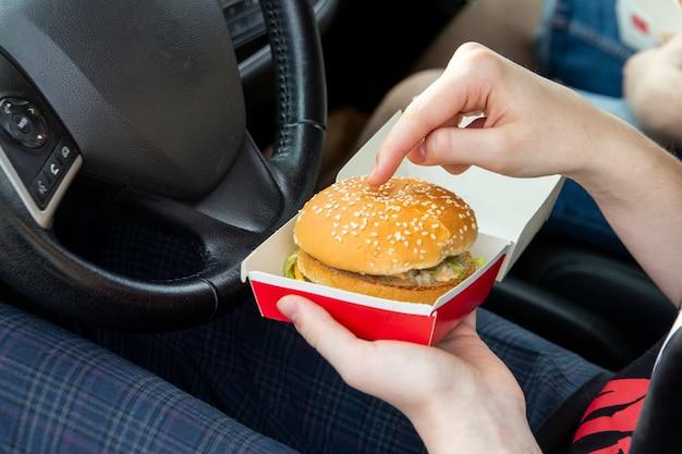 La fille dans la voiture tient un hamburger dans ses mains snacks à emporter de restauration rapide sur la route