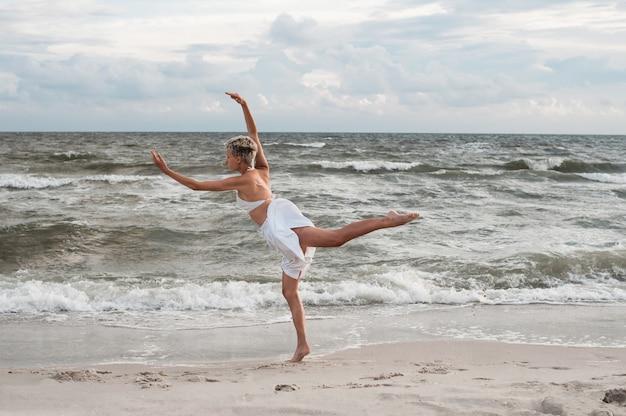 La fille danse sur la plage