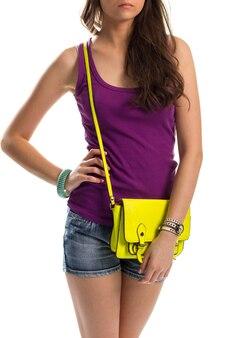 Fille en débardeur violet. sac lime et short en jean. un modèle attrayant porte une tenue d'été. belle combinaison de couleurs.