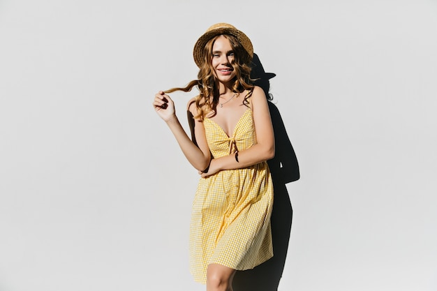 Fille debonair en tenue jaune jouant avec ses cheveux bouclés brillants. intéressé femme gracieuse posant en chapeau d'été.