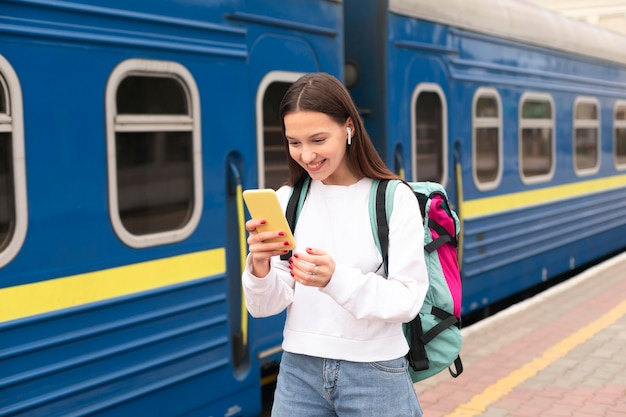 Fille debout à côté du train et à l'aide de téléphone mobile