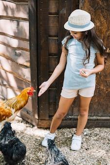 Fille debout dans la ferme nourrir les poules