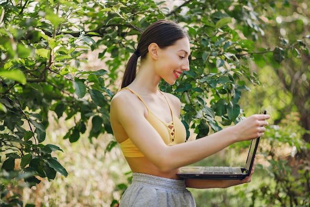Fille debout dans un parc d'été et tenant un ordinateur portable dans ses mains