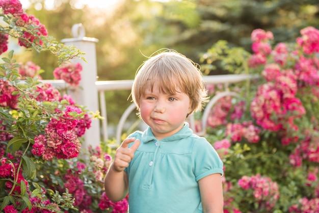 Fille debout près des rosiers. le concept d'allergie