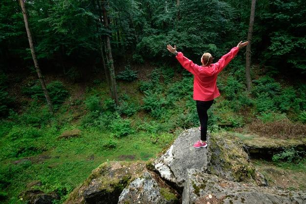Fille debout sur un rocher dans une forêt. travel.g