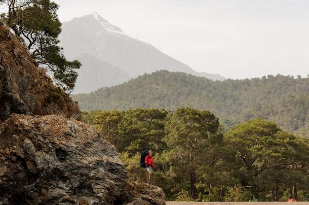 Fille debout sur le rocher avec sac à dos de randonnée et bâtons de marche