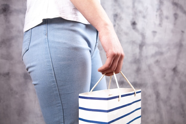 Fille debout avec un sac cadeau